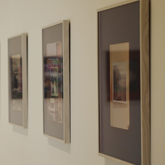 Exhibition image of framed pictures on a wall